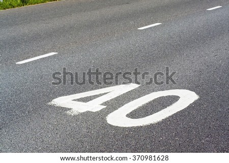 speed limit painted on tarmac - stock photo