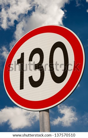 Speed limit sign against a blue sky.
