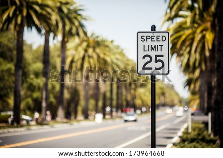 Speed Limit 25 sign on the road with palms, USA - stock photo