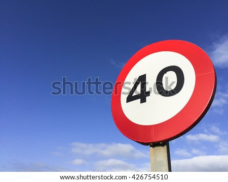 Speed limit signpost forty against blue sky.