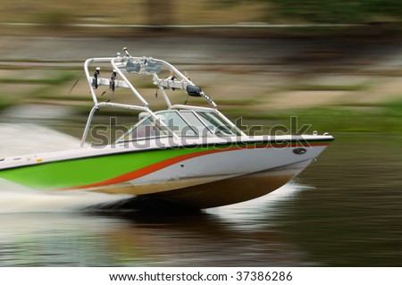 Speed motor boat cruising in the river. Motion blurred panning shot. - stock photo