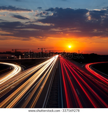 Speed Traffic at Sundown Time in the city - light trails on motorway highway at dusk, long exposure, urban background - stock photo