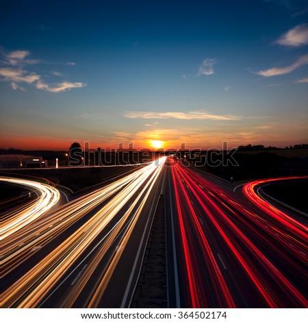 Speed Traffic light trails on motorway highway at sundown, long exposure, urban background with sun and dark sky - stock photo