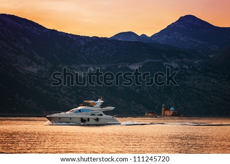speedboat in the sunset sea on mountains background. Montenegro - stock photo