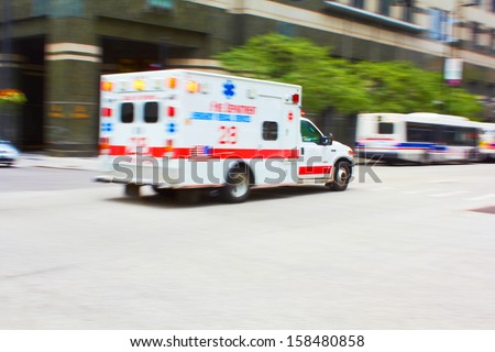 Speeding Ambulance to the Rescue in the City, motion blurred to add speed effect. - stock photo