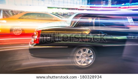 Speeding car and yellow taxi cab in a blurred night - Traffic jam in New York City - Times Square Manhattan downtown - stock photo