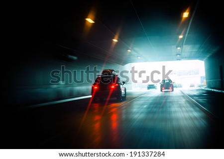 Speeding car inside a highway tunnel exiting to white calm light - stock photo