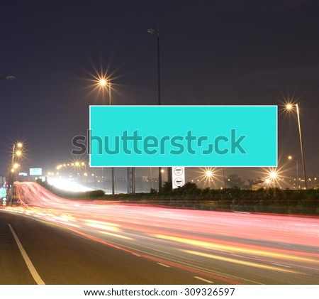 Speeding cars on modern Road infrastructure with blank hoarding for text messages, artistic long exposure shot