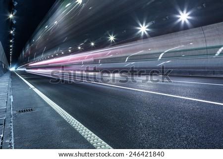 speeding lights of cars in city at night. - stock photo