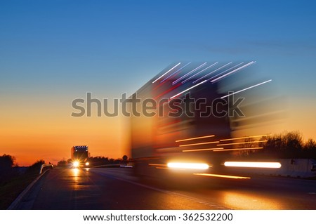 Speeding motion blur oncoming trucks with glowing lights on the highway after sunset. Shining the spotlight cars. Blue and orange bright sky at dusk. - stock photo