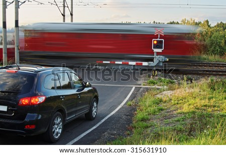 Speeding motion blur red train passing through a railway crossing with gates. Black car standing in front of the railway barriers on an asphalt road. - stock photo