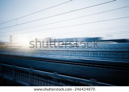speeding train away from railway station, shanghai china. - stock photo