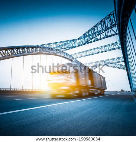 speeding truck go through the bridge. - stock photo