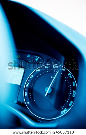 Speedometer close-up with the needle pointing a high 140 km/mph speed, blur effect and blue tone to depict high speed concept and security driving - stock photo