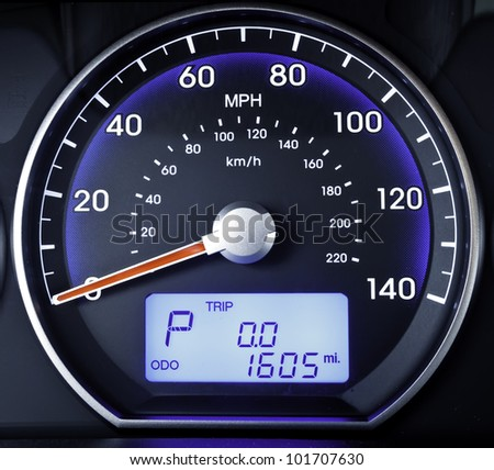 Speedometer in parked car, with LCD display of odometer and trip calculator - stock photo