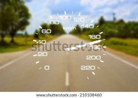 Speedometer over a blurred road representing driving very fast - stock photo