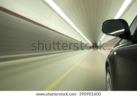 Speedy car driving in tunnel.