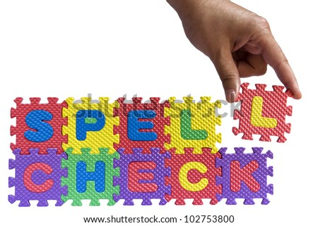 Spell check concept - alphabet puzzle letters and hand isolated on white background - stock photo