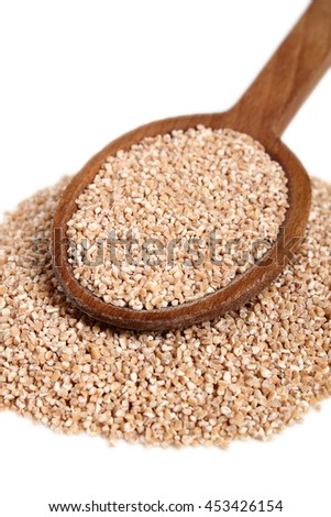Spelt groats on wooden spoon. Isolated on white background.