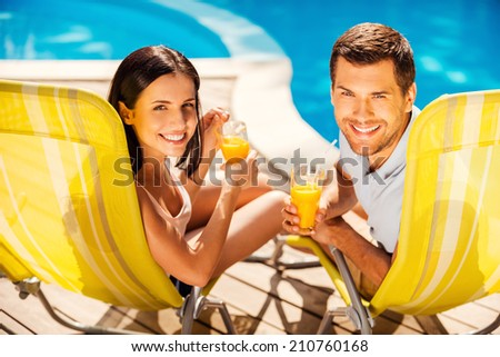 Spending carefree time poolside. Happy couple holding cocktails and smiling while sitting at the deck chairs by the pool - stock photo