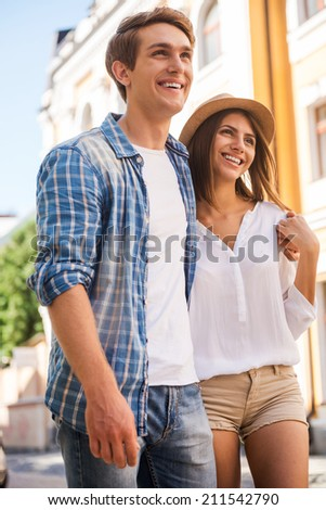 Spending free time together. Beautiful young loving couple walking along the street and smiling  - stock photo