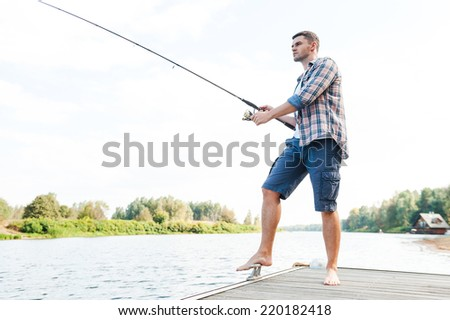 Spending good time fishing. Full length of confident young man fishing while standing on quayside