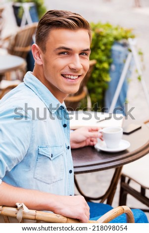 Spending good time in cafe. Rear view of cheerful young man drinking coffee and looking over shoulder while sitting in sidewalk cafe - stock photo