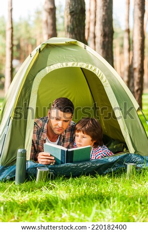 Spending good time outdoors. Father and son reading book while lying in tent together - stock photo
