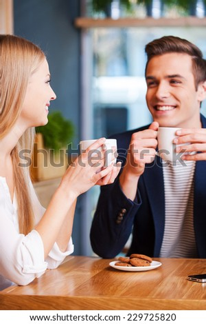 Spending good time together. Beautiful young couple talking to each other and smiling while enjoying coffee in cafe together  - stock photo