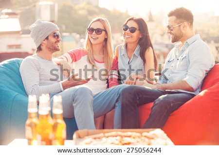 Spending great time together. Four young cheerful people chatting while sitting at the bean bags on the roof of the building with pizza and beer laying on foreground - stock photo