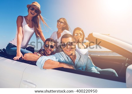 Spending great time together! Group of young happy people enjoying road trip in their white convertible and smiling at camera - stock photo