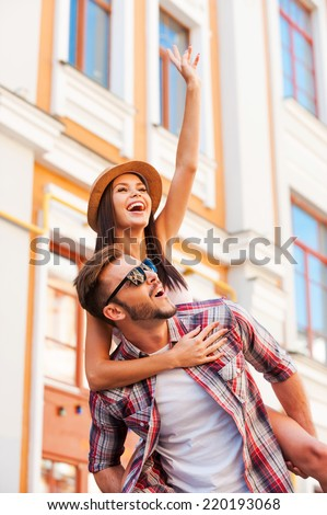 Spending great time together. Happy young man carrying his beautiful girlfriend on shoulders and smiling while walking by the street - stock photo