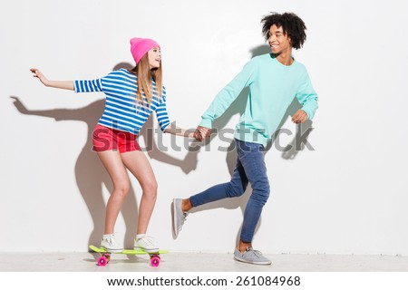 Spending great time together. Happy young women riding on skateboard while her boyfriend running near against white background - stock photo