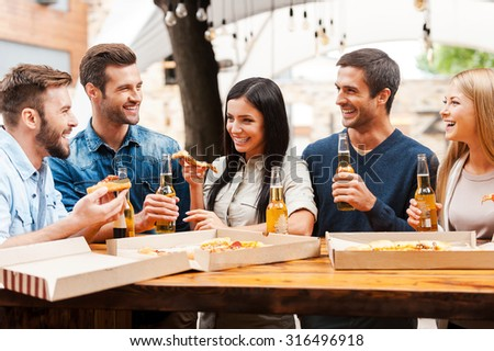 Spending great time with friends. Group of joyful young people eating pizza and drinking beer while standing outdoors - stock photo