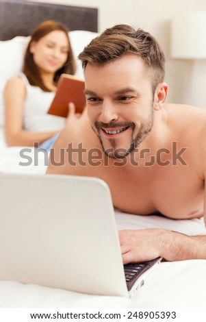 Spending leisure time in bed. Handsome young and shirtless man lying in bed and working on laptop while woman reading a book in the background