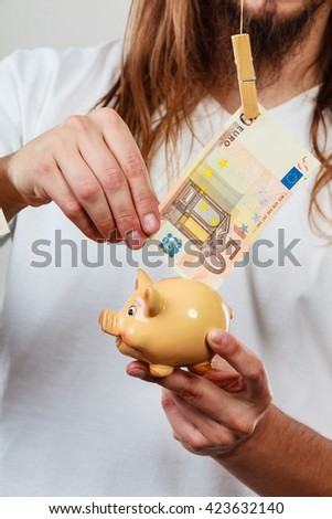 Spending money concept. Male hands with piggybank and euro banknote cash. Savings. - stock photo