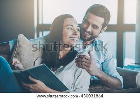 Spending nice time at home. Beautiful young loving couple bonding to each other and smiling while woman holding a book - stock photo
