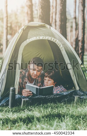 Spending nice time outdoors. Father and son reading book while lying in tent together - stock photo
