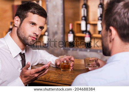 Spending night in bar. Two confident young men in shirt and tie talking to each other and gesturing while drinking whisky at the bar counter  - stock photo