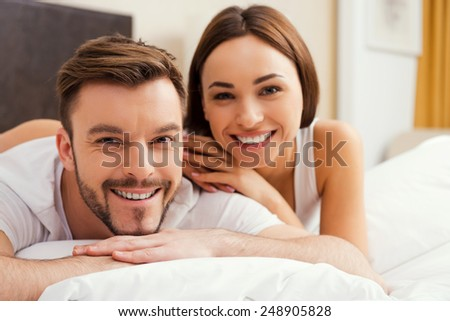 Spending quality time together. Beautiful young loving couple bonding to each other while lying in bed together - stock photo
