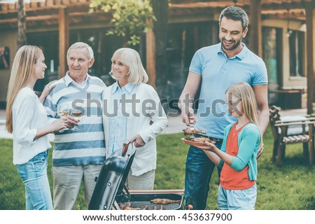 Spending quality time with family. Happy family of five people barbecuing meat on grill on the back yard - stock photo