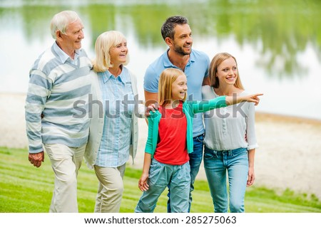 Spending quality time with family. Happy young family walking outdoors together while little girl pointing away and smiling