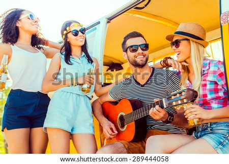 Spending quality time with friends. Handsome young man sitting at minivan and playing guitar while three girls standing close to him and smiling  - stock photo