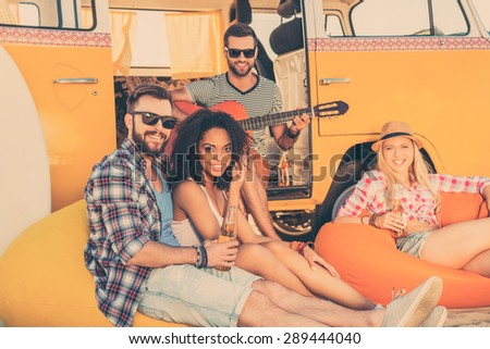 Spending summer time together. Three happy young people sitting near their minivan with beer bottles while man playing the guitar  - stock photo