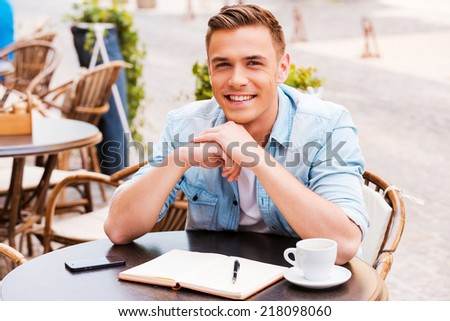 Spending time in cafe. Confident young man looking at camera and smiling while sitting in sidewalk cafe - stock photo