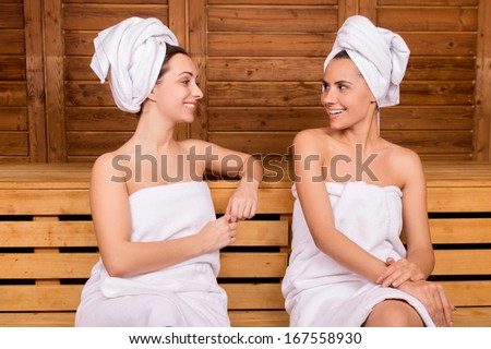 Spending time in sauna. Two attractive women wrapped in towel talking to each other while relaxing in sauna - stock photo