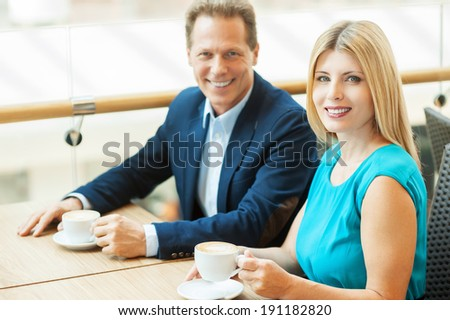 Spending time together. Beautiful mature couple drinking coffee together and looking at camera while sitting in coffee shop - stock photo