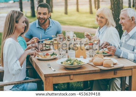Spending time with family. Happy family of five people communicating and enjoying meal together while sitting at the dining table outdoors - stock photo