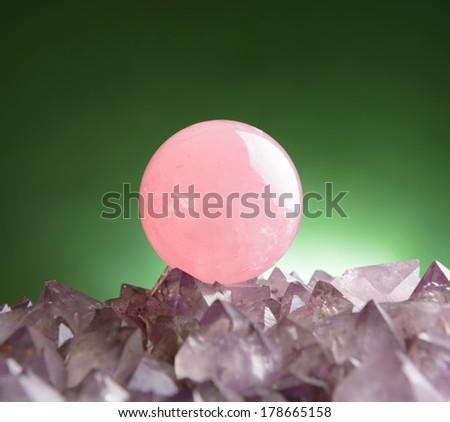 Sphere of rose quartz natural crystal on amethyst rock - stock photo