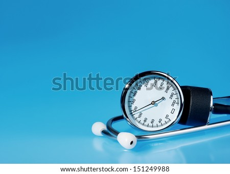 Sphygmomanometer and stethoscope on blue, reflective background  - stock photo